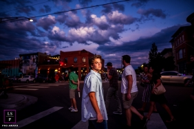 teen boy crosses the street during blue hour during a teen lifestyle photo shoot