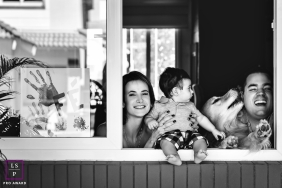 Family lifestyle photo in quarantine shot from the outside of their house and the family inside looking out window