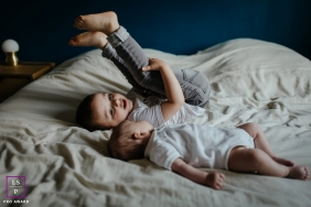 Auvergne-Rhone-Alpes family photography of sibling playing on a bed