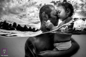 Rio de Janeiro family portrait of father and daughter partially submerged in water with a moody sky