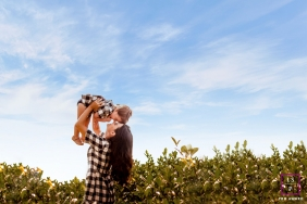 A mother holds up her baby above her in this Minas Gerais lifestyle family portrait