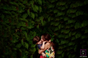 A mother hugs her child between the leaves of a large plant in this Minas Gerais family portrait