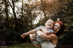 France lifestyle family photography of mom holding son pretending to fly