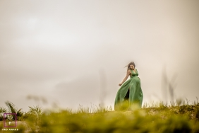 Brazil Maternity Portrait of woman in long dress posing in a wind-blown field
