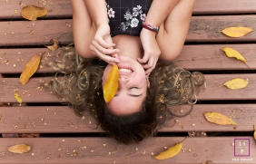 A young teen lays on a deck with leaves around her and one placed to cover her left eye | Rio de Janeiro lifestyle teen photography