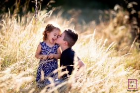Pays de la Loire family photo session with a brother kissing his sister on the cheek amongst tall grasses
