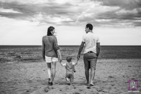 A couple and their toddler walk toward the ocean on the sand during a lifestyle photoshoot in France