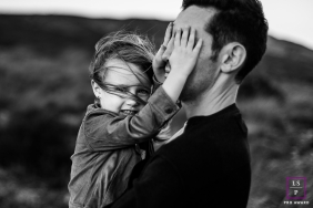 Hide and seek with daddy, girl covers her father's eyes in this French family portrait