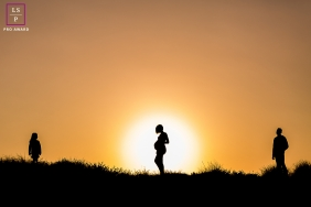 A sunset portrait of a family silhouetted against an orange sky in France