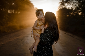 Mom and daughter stand on a dirt road at sunset for a lifestyle portrait in Minas Gerais