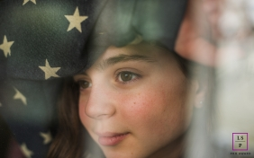 New Jersey Lifestyle portrait of a young woman looking out a window under fabric of blue with white stars
