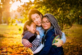 Two girls enjoy a sweet hug from their mohther in the afternoon sunlight