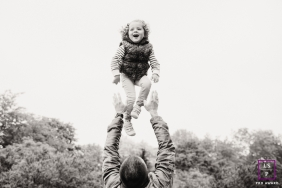 A young girl is thrown in the air by her father during a family lifestyle session