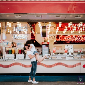 French couple portrait in front of a food vendor at a fair