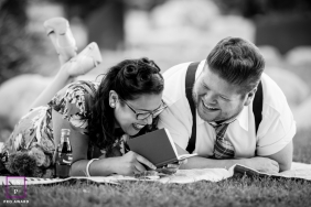 A couple shares a laugh while relaxing and reading on a blanket on grass in California