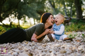 A mother lies in small rocks with her toddler, laughing during this France Lifestyle Portrait Session