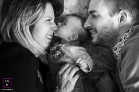 A couple with their baby boy lie down for a portrait, while baby takes a bite from mom's nose | Limoges Lifestyle Photography