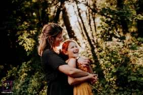 A France mother / daughter portrait in nature with trees and a splash of sunlight