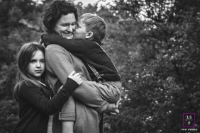 France Famly Photography | Mom with her daughter and son, who is giving her a kiss, stand for a lifestyle portrait