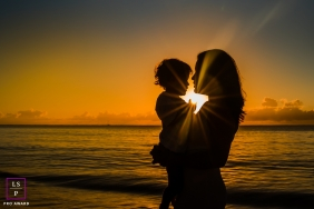 A mother holds her young child by the wateredge at sunset in Brazil