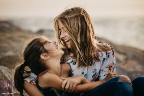 Sisters sharing a laugh during a family session in Castelldefels, Spain