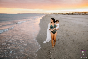 Herault lifestyle beach maternity photography in Occitanie with a mum-to-be and toddler walking on the sand by the water at sunset