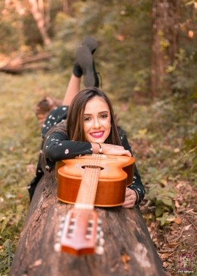 Brazil Girl lying on top of her guitar, smiling at the camera during a Santa Catarina lifestyle shoot