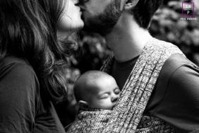 London England lifestyle couple photo session with a kiss and a baby sleeping between them