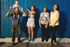 Brazil lifestyle family portrait session against a solid blue wall in Rio Grande do Sul with a crying baby and four adults