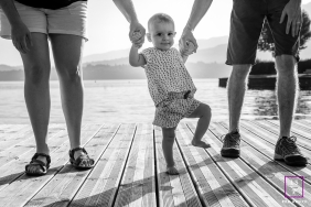 A Savoie baby girl is held upright by her parents' hands during a lifestyle family portrait session in Auvergne-Rhone-Alpes