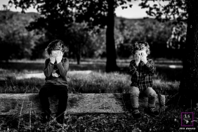 Pyrenees-Orientales siblings play Hide and seek in this black and white lifestyle portrait from a park in Perpignan