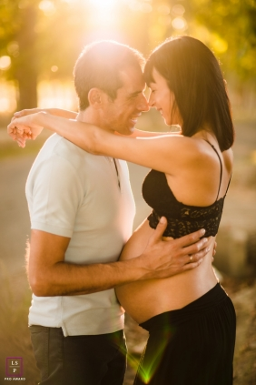 A Spain Pregnancy photo at sunset with a young couple in a park of Madrid