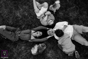 A Santa Catarina Family playing on the grass with their dogs in this overhead lifestyle portrait in Florianopolis