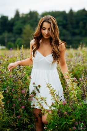 Vertical picture of Seattle girl walking through tall grass for a teen portrait in Washington