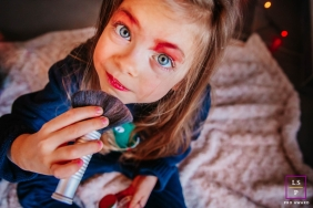 France Lifestyle Photographer created this artistic portrait of The little girl putting on make-up