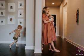 Tennessee Lifestyle Photographer created this artistic portrait of a mother with her newborn and young son running in their home session