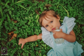 Minas Gerais Lifestyle Photographer created this artistic portrait of a little girl laying in the grass with her bottle