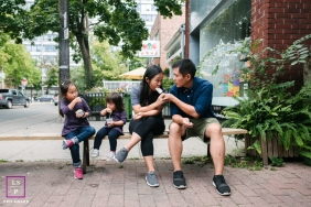 Ontario Family posing for a Lifestyle portrait while eating ice cream just outside their favorite ice cream store in Toronto