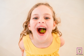 Maceio young girl poses for a Lifestyle Portrait Session while smiling  with open mouth and candy on her tongue