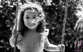 Maceio young girl poses for a Lifestyle Portrait Session smiling while she swings at the park