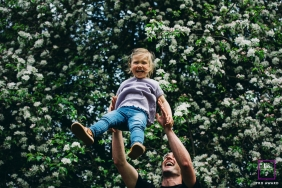 London Father and child posing for a Lifestyle portrait with a tree full of flowers at their backdrop