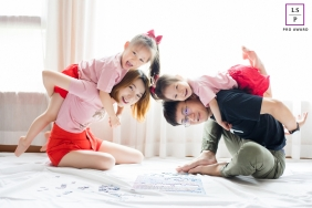 Hangzhou City Family posing for a Lifestyle portrait in a brightly lit room at home