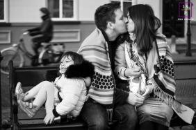 Netherlands Family posing for a Lifestyle portrait as their daughter suddenly appeared and she climbed into the chair and leaned back against her father and sang and The couple kept kissing, a bicycle kept going through the background