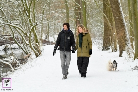 Utrecht couple posing for a creative Lifestyle image walking hand in hand in the snow with their two little dogs