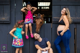 Parana family pose for a lifestyle maternity photo session at the barn with their horse