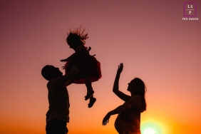 Curitiba family pose for a lifestyle portrait with mom and dad playing with their daughter in the sunset