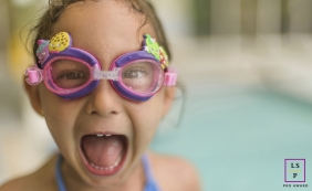 New Jersey girl poses for a lifestyle photograph with fun goggles on her face while at the pool