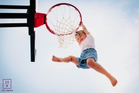 Auvergne-Rhone-Alpes young girl poses for a lifestyle image as she plays while hanging on to her daddy's basketball hoop