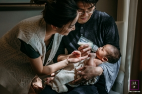 Texas Family posing for a Lifestyle portrait as a couple feed their newborn baby with a bottle