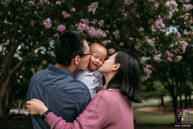 Austin Family posing for a Lifestyle portrait as mom and dad snuggle and kiss their son